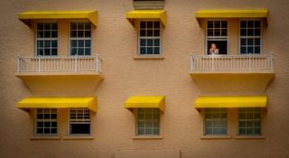 person looking out of apartment window with yellow awnings