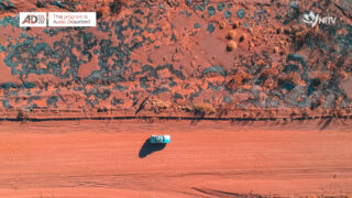 Aerial shot of a blue car driving along a red dirt track with desert plants along the side of the road. The audio description logo is in the top left corner, accompanied by the words 'this program is audio described'. The NITV logo is in the top right hand corner. It is an abstraction of a campfire constructed from pieces of the SBS logo.