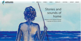 image from behind a person with no shirt on holding a fishing spear looking out into the blue ocean